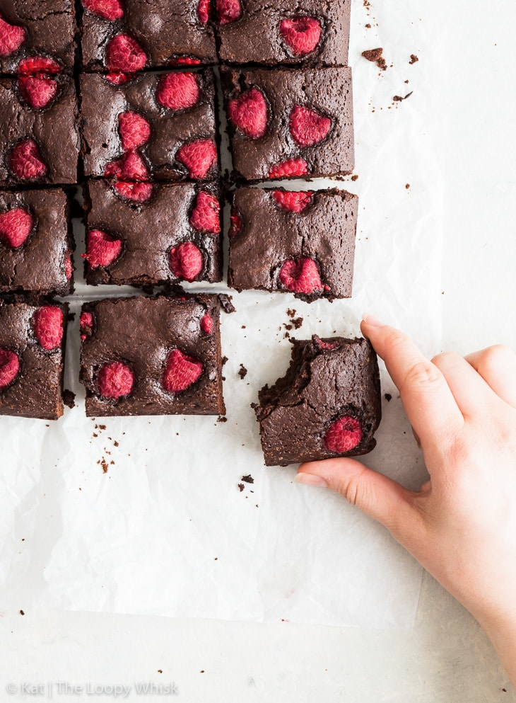 Overhead view of gluten free chocolate brownies with raspberries, one brownie has had a bite taken out of it and a hand is holding it.
