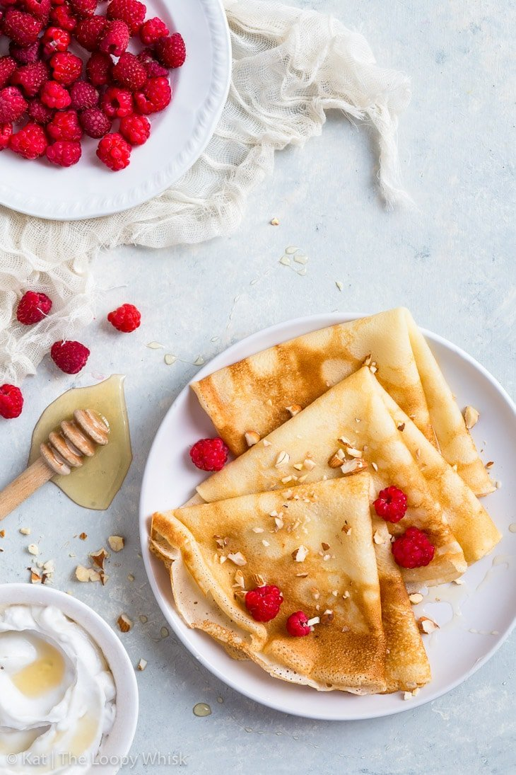 Gluten free crepes, folded into triangles, on a white plate, served with raspberries, a drizzling of honey and some chopped almonds. A bowl of cream and a plate of raspberries complete the picture.
