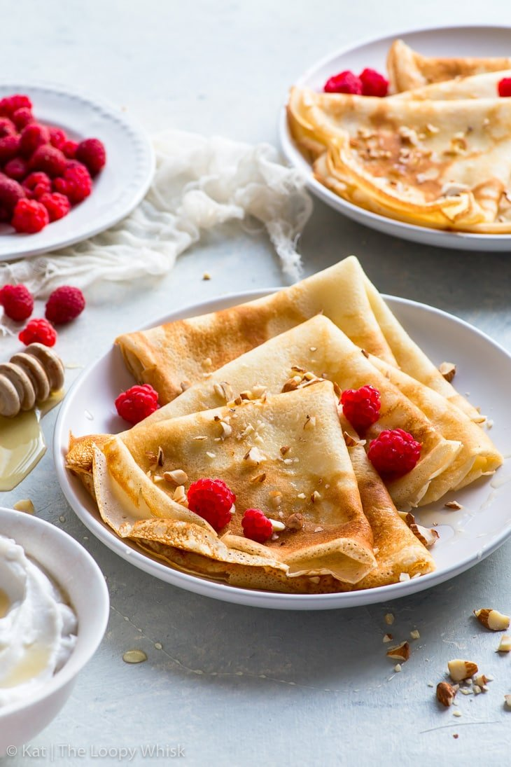 Gluten free crepes, folded into triangles, on a white plate, served with raspberries, a drizzling of honey and some chopped almonds. A bowl of cream, a plate of raspberries and another plate with French crepes complete the picture.