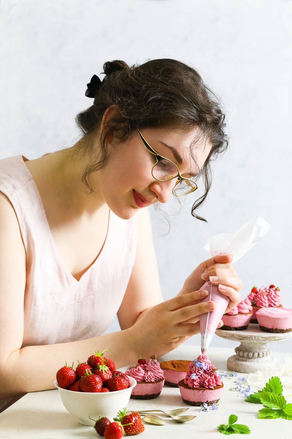 The author of The Loopy Whisk food blog, Kat, in the process of decorating raw vegan strawberry cupcakes.