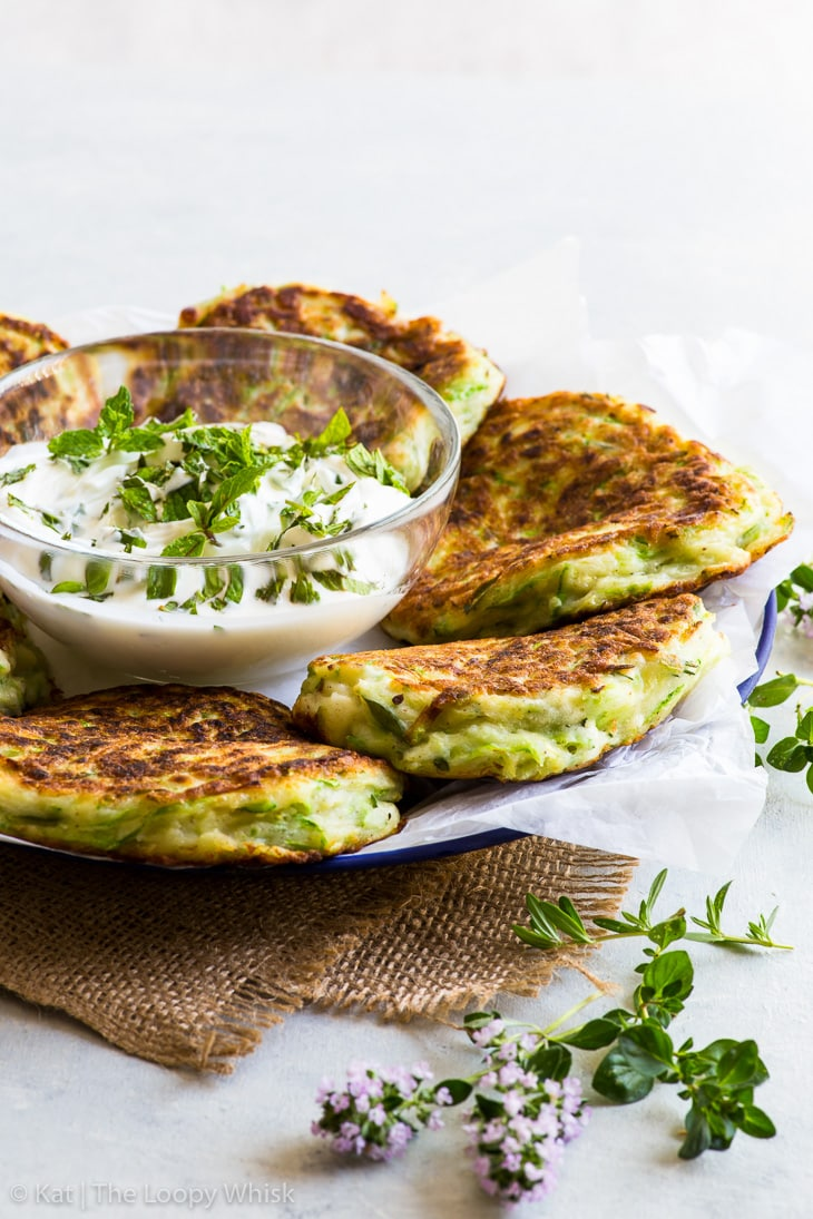 Mozzarella stuffed zucchini fritters on a plate with a bowl of greek yogurt in the middle.