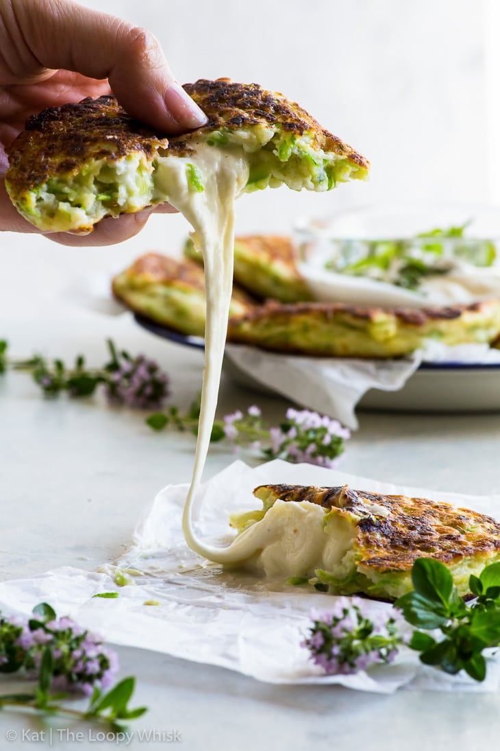 Mozzarella cheese pull: the zucchini fritter has been torn in half, and the melted mozzarella is gooey, stretching between the two halves of the fritter.