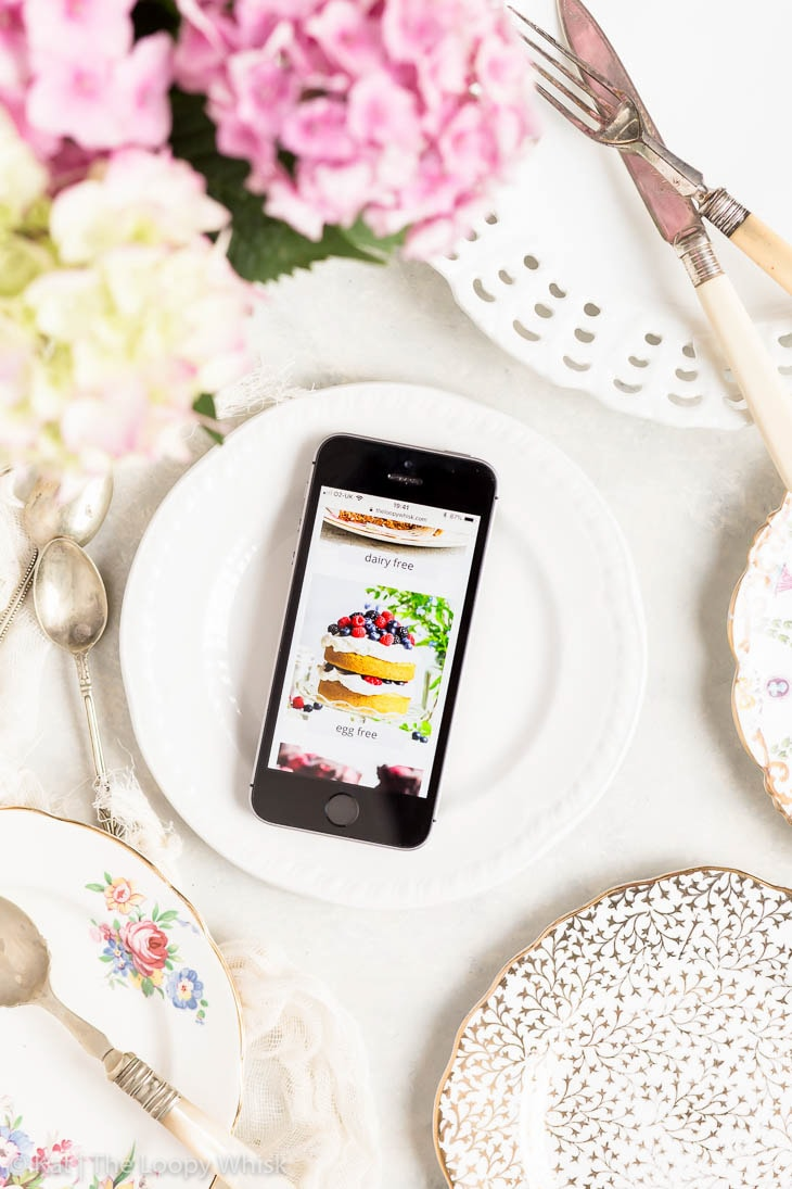Flatlay photo with decorative antique plates, flowers, antique cutlery and a smartphone showing the redesigned The Loopy Whisk website.