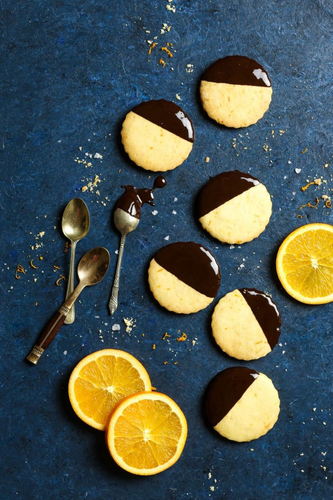 Food flat lay of gluten free chocolate dipped orange cookies on a dark blue background, with a few orange slices arranged around them.