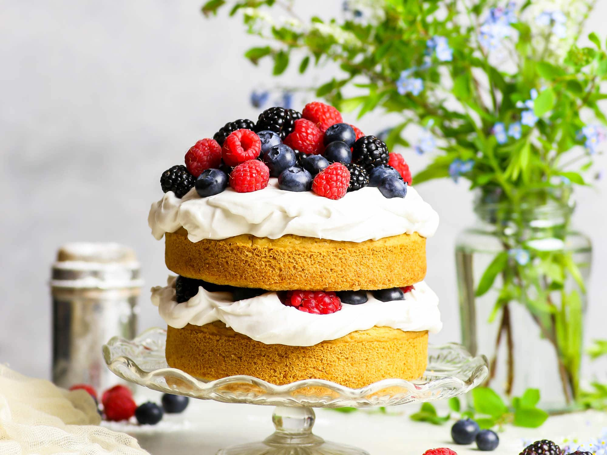 Gluten free vegan vanilla layer cake with summer berries and coconut cream frosting on a glass cake stand. A vase full of foliage and flowers is in the background.