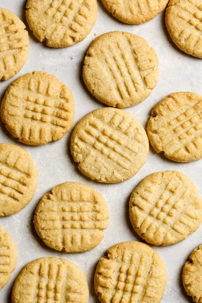 Overhead shot of peanut butter cookies, with their typical criss-cross pattern made with a fork.