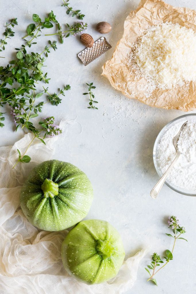 The ingredients required for gluten free zucchini fritters, on a light blue background.
