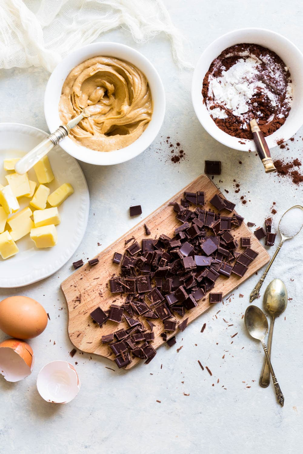 Overhead shot of the ingredients required for peanut butter stuffed brownie cookies on a light greyish blue surface.