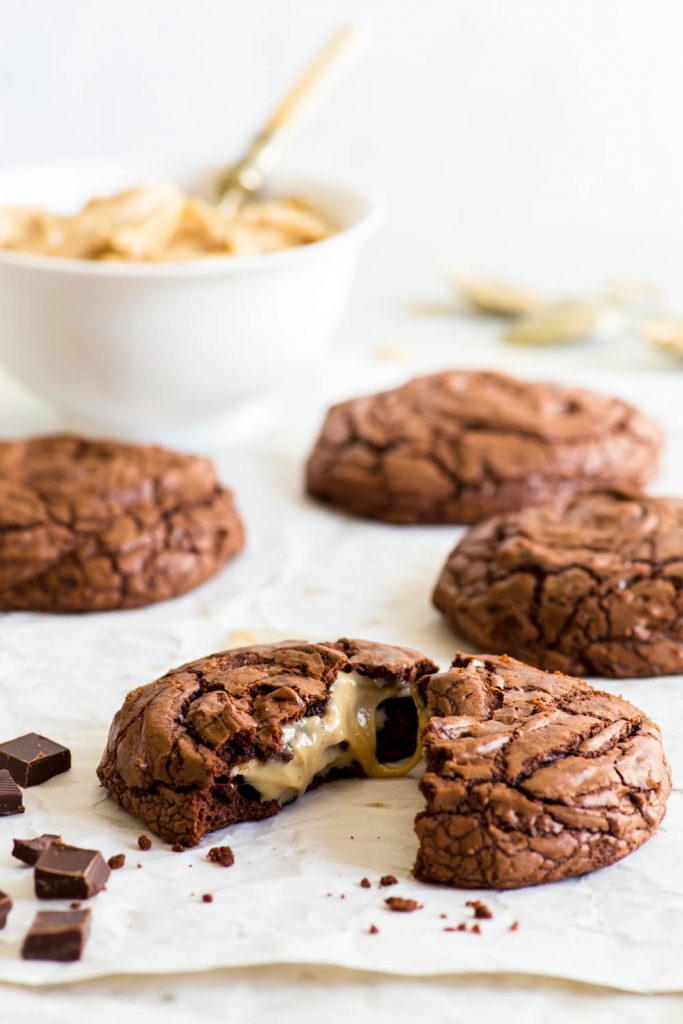 Peanut butter stuffed brownie cookies on a large piece of white parchment paper. A bowl of peanut butter is in the background. The frontmost cookie has been broken in half, exposing its ooey gooey peanut butter centre.