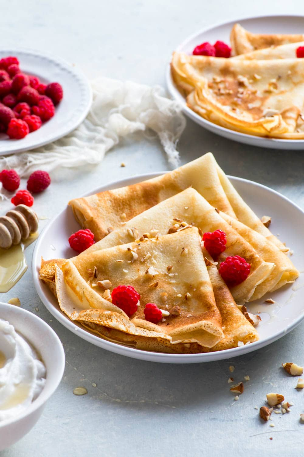 Gluten free crepes, folded into triangles, on a plate, drizzled with honey, sprinkled with chopped nuts and served with coconut cream and fresh raspberries.