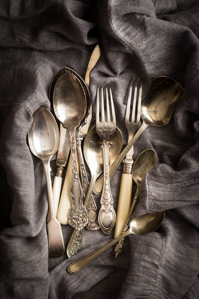 Antique spoons, forks and knives on a dark grey napkin.