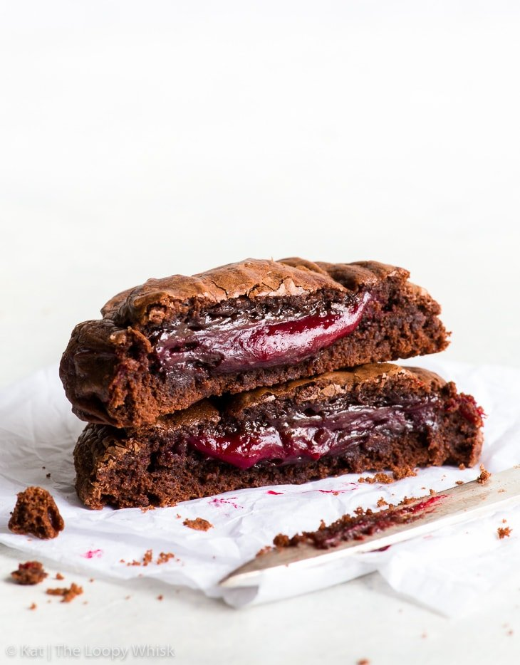 Two hales of a raspberry stuffed brownie cookie, stacked one on top of the other, with the fudgy middle exposed. The raspberry centre is oozing out, looking utterly decadent.