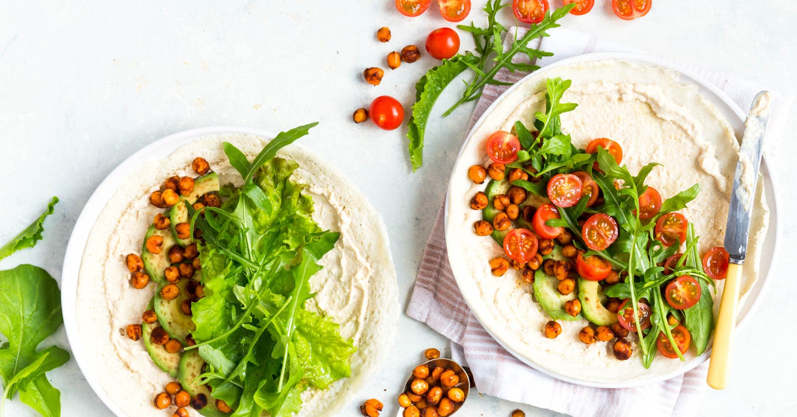 Overhead shot of gluten free veggie wraps on a white surface. The veggie wraps consist of thin crepes, hummus, lettuce leaves, cherry tomatoes and spicy chickpeas.