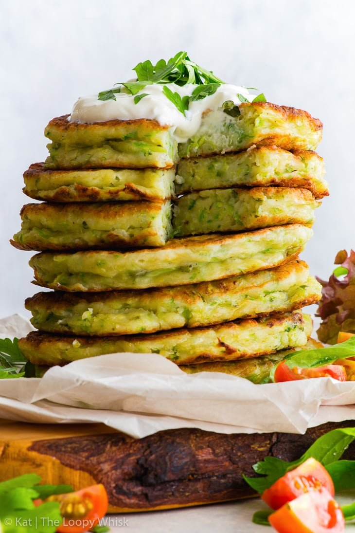 A stack of gluten free zucchini fritters, with a dollop of yoghurt on top, sprinkled with some chopped parsley. The stack stands on some parchment paper on a wooden cutting board. A few pieces of the fritters have been cut away.