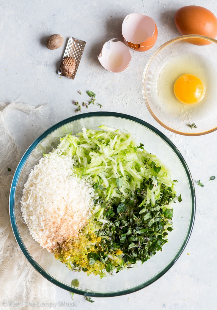 The grated zucchini in a large glass bowl. The chopped thyme, lemon zest, grated nutmeg and parmesan cheese have been added to the bowl. A smaller bowl with a cracked egg is next to the larger bowl.