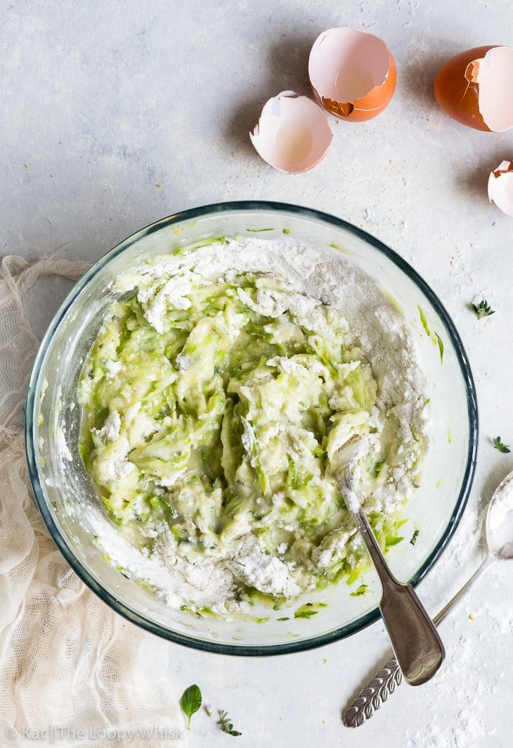 All the ingredients for the gluten free zucchini fritters in a large glass bowl, partially mixed together with a fork. The flour hasn't been fully mixed in, some flour clumps remain. Cracked egg shells and a spoon complete the picture.