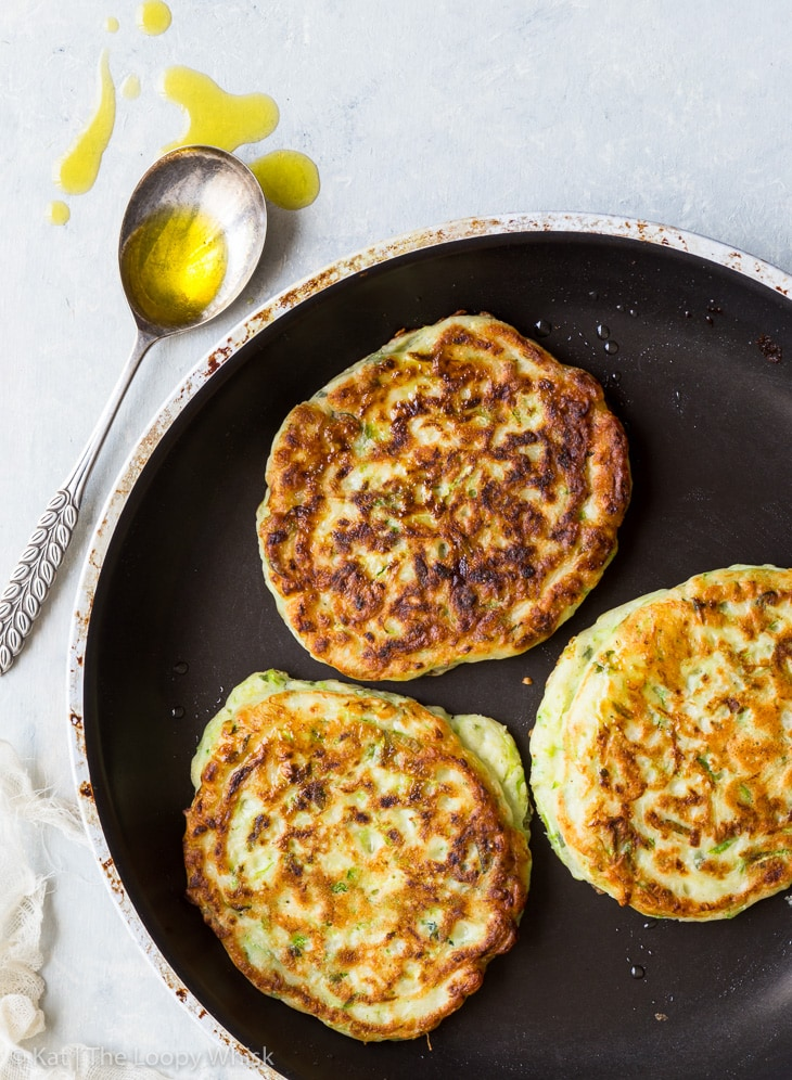 Three gluten free zucchini fritters in a nonstick pan. A spoon with olive oil is next to the pan.