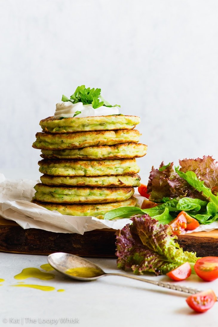 A stack of gluten free zucchini fritters, with a dollop of yoghurt on top, sprinkled with some chopped parsley. The stack stands on some parchment paper on a wooden cutting board. A few salad leaves, cherry tomatoes and a spoon complete the picture.