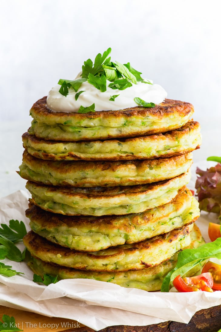 A stack of gluten free zucchini fritters, with a dollop of yoghurt on top, sprinkled with some chopped parsley. The stack stands on some parchment paper on a wooden cutting board.