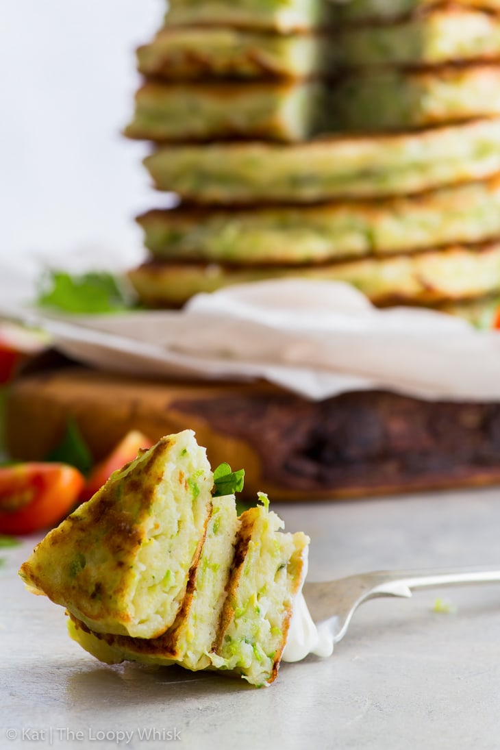 A stack of gluten free zucchini fritters on some parchment paper on a wooden cutting board. A few pieces of the fritters have been cut away, and are o a fork in the foreground.