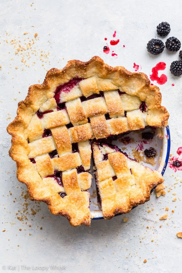 Overhead shot of the blackberry pie with a decorative lattice. A few pieces have been cut already.
