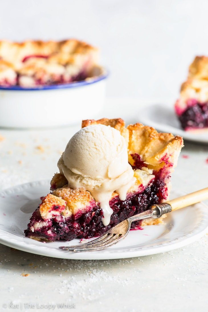 A piece of blackberry pie with a scoop of ice cream on a plate.