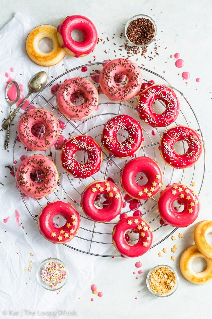 Overhead shot of cake donuts wth a vibrant pink raspberry glaze on a cooling rack, decorated with sprinkles.
