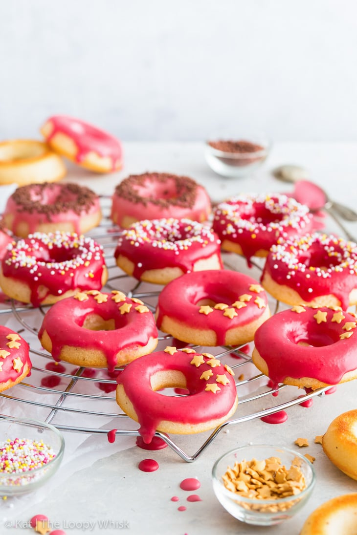 Raspberry glazed cake donuts on a cooling rack, decorated with sprinkles.