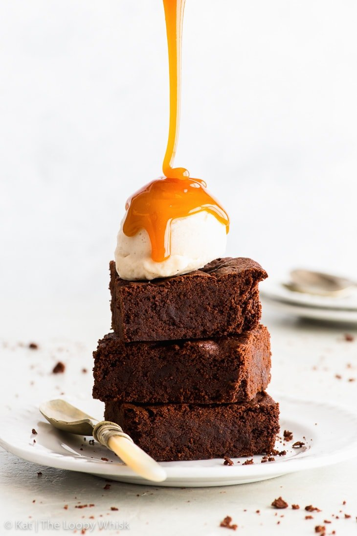 A stack of three vegan chocolate brownies on a white plate, with a scoop of ice cream on top, being generously drizzled with a caramel sauce.