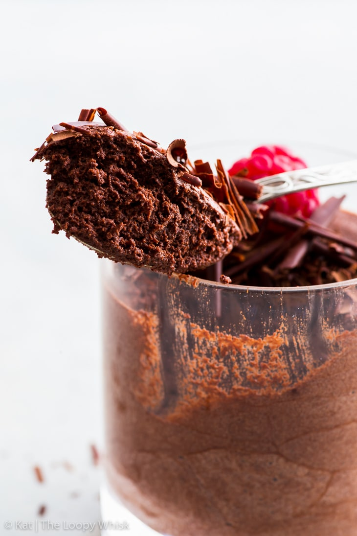 Vegan chocolate mousse on a spoon, showing its airy fluffy texture.