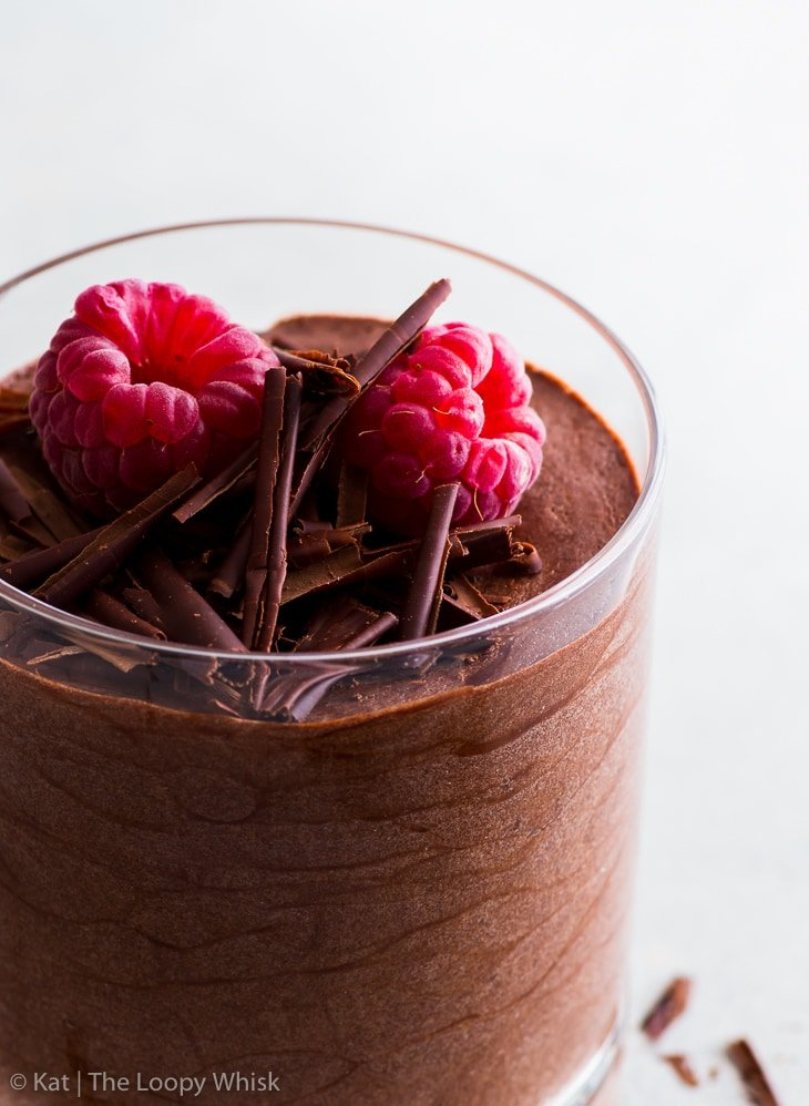 Vegan chocolate mousse in a glass with chocolate shavings and raspberries. Close-up photo.