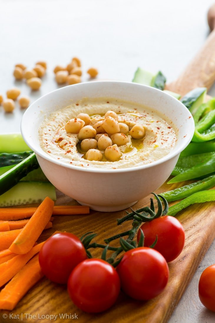 Creamy homemade hummus in a small white bowl, topped with olive oil, chickpeas and a pinch of smoked paprika. It is part of a veggie platter.