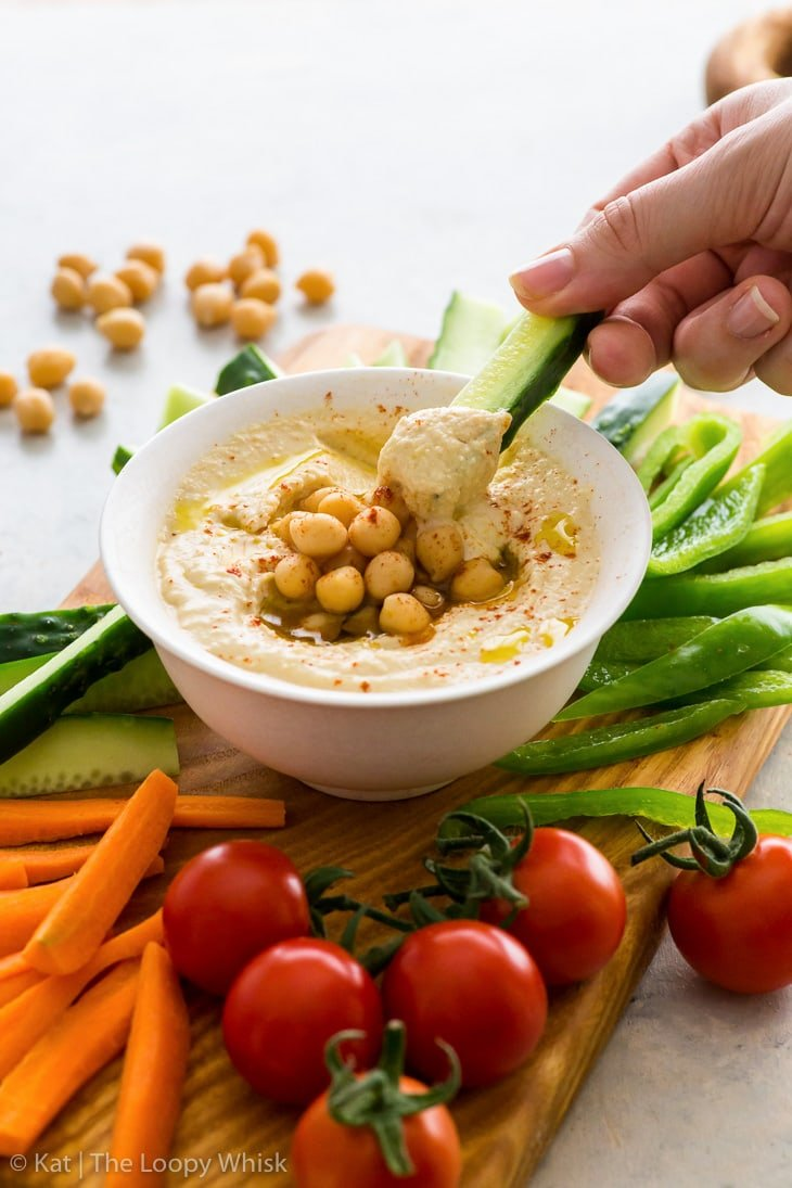 Creamy homemade hummus in a small white bowl, topped with olive oil, chickpeas and a pinch of smoked paprika. It is part of a veggie platter, and is currently being scooped up with a cucumber stick.