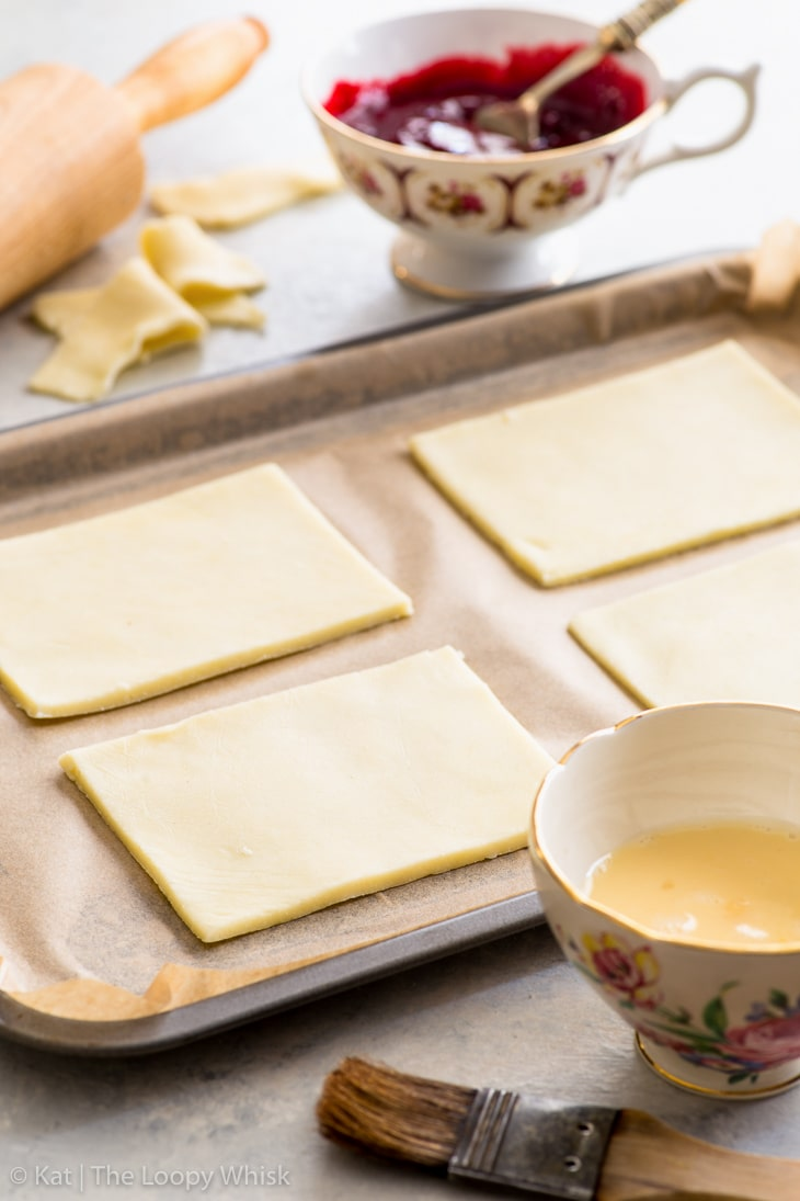 Process of making gluten free pop tarts: pie dough rectangles on lined baking sheet.