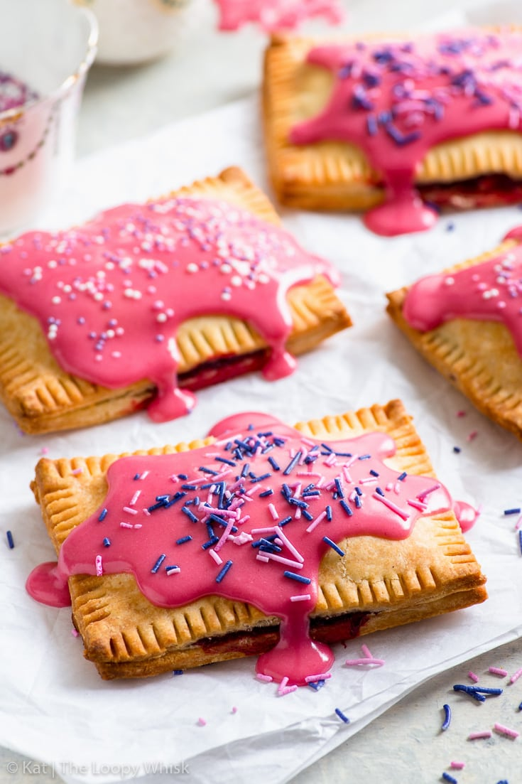 Gluten free pop tarts decorated with vibrant pink raspberry frosting and sprinkles, on a white surface.