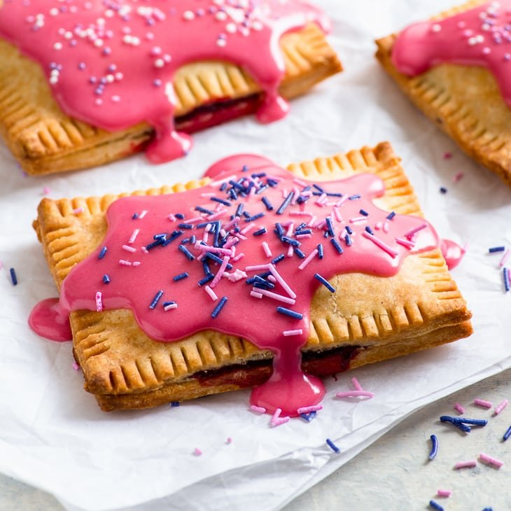 Raspberry Glazed Gluten Free Pop Tarts - With naturally dyed vibrant pink frosting, these raspberry glazed gluten free pop tarts are as pretty as they are delicious! Plus, they're super easy to make. Gluten free dessert recipes. Homemade pop tarts. Raspberry pop tarts. Pop tart recipe. Gluten free pie crust. Easy dessert recipes. Pop tarts flavors. Pie recipes. Easy recipes. #glutenfree #dessert #recipe #poptarts