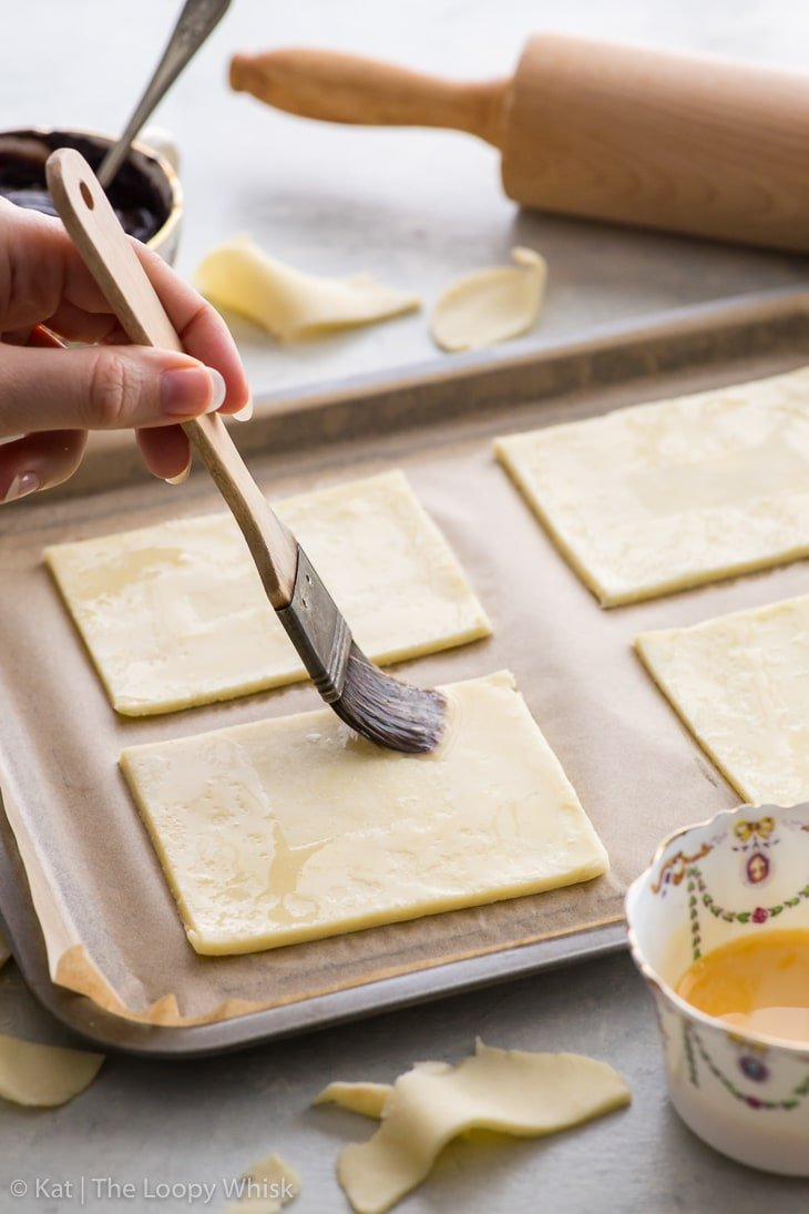 The process of making s'mores pop tarts: egg washing the edges of pie dough rectangles.