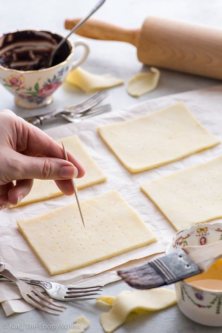 The process of making s'mores pop tarts: pricking the top rectangles with a toothpick.
