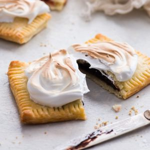 S'mores Pop Tarts (Gluten Free) - How to take the humble pop tart to new heights: make s'mores pop tarts by stuffing them with chocolate and smothering them with marshmallow meringue frosting. Now doesn't that sound heavenly? Pop tart recipe. S'mores dessert recipe. Marshmallow desserts. Swiss meringue. Gluten free dessert recipes. Easy dessert ideas. Gluten free pie crust. Gluten free pie dough. #poptarts #smores #chocolate #marshmallows #meringue #glutenfree #dessert #recipes