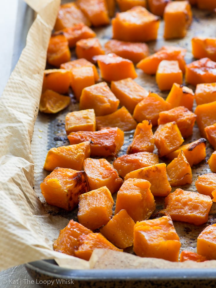 Close-up of chunks of roasted butternut squash on a baking tray lined with greaseproof paper.