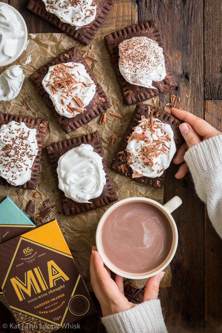 Overhead shot of hot chocolate pop tarts on a brown wooden table. A cup of hot chocolate with marshmallow is held in one hand, and a pop tart in the other. MIA chocolates in the lower left corner.