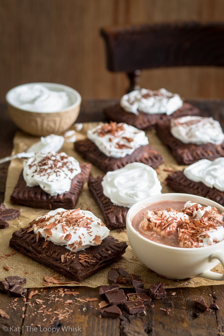 Hot chocolate pop tarts on a brown wooden table, with a cup of hot chocolate next to them.