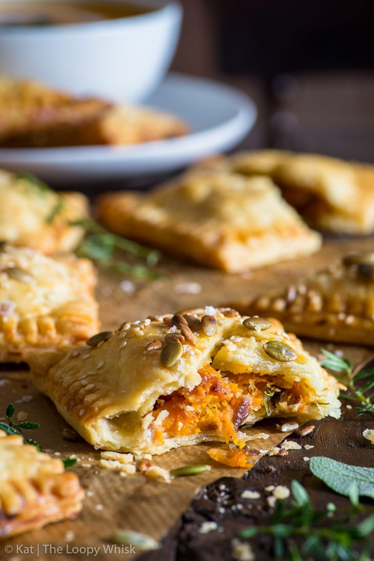 Close-up of a pumpkin flaky pastry torn in half, exposing its vibrant orange pumpkin, caramelised onion and cheddar filling.