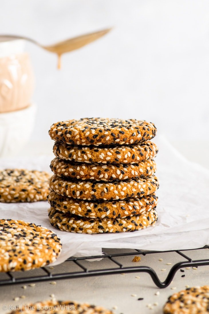 Stack of vegan tahini cookies on white parchment paper on top of black cooling rack.