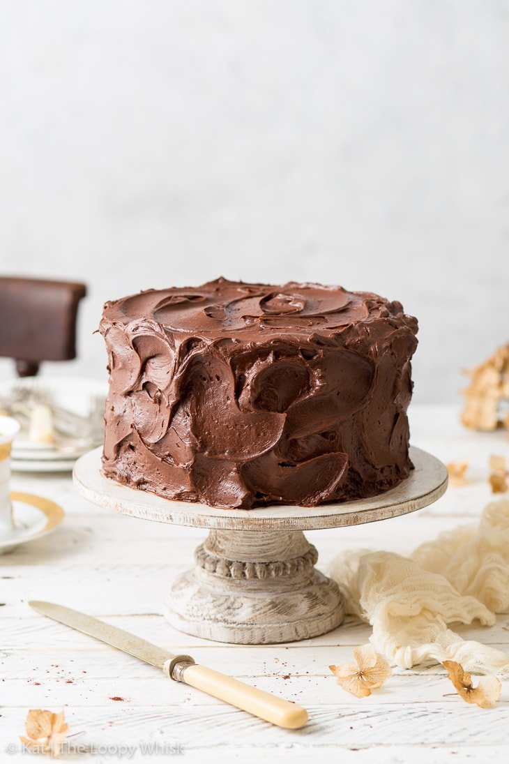 Gluten free chocolate cake, decorated with swirls of chocolate buttercream frosting, on a decorative cake stand.