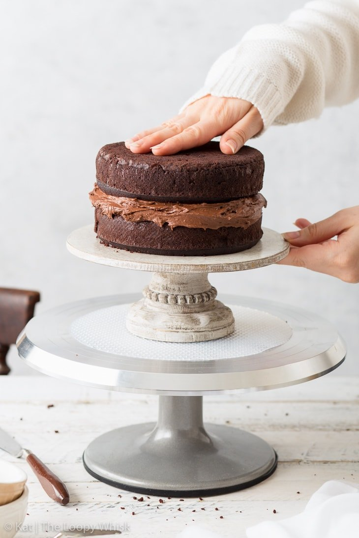 Assembling the gluten free chocolate cake by placing the second sponge on top of the frosting layer.
