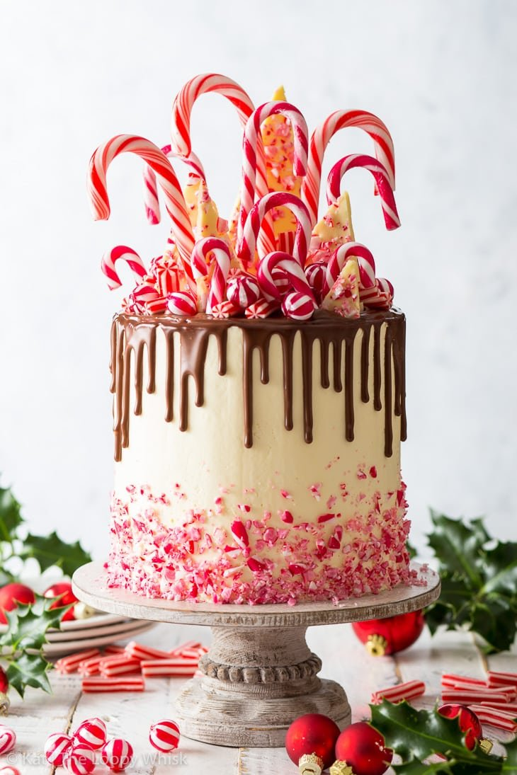 Candy cane cake on a white decorative cake stand, surrounded by sprigs of holly, more candy canes and red Christmas baubles.