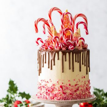 Candy Cane Cake (Gluten Free) - This might very well be the ultimate Christmas cake. With melt-in-the-mouth chocolate sponges, fluffy Swiss meringue buttercream frosting, a luscious chocolate ganache drip and a small forest of candy canes on top… this candy cane cake is dressed to impress. Christmas recipes. Christmas dessert ideas. Christmas baking. Holiday baking ideas. Gluten free cake. Gluten free chocolate cake recipe. Chocolate drip cake. Layer cake recipe. #christmas #cake