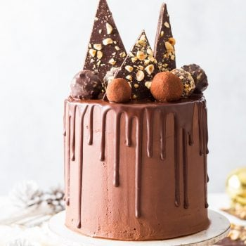Luxurious Vegan Chocolate Truffle Cake [SPONSORED] - On a scale of deliciousness from 1 to 10, this vegan chocolate truffle cake is off the charts. With melt-in-the-mouth chocolate sponges, fluffy vegan chocolate frosting and absolutely stunning decorations, it's the perfect showstopper for all occasions. Vegan chocolate cake. Vegan cake recipes. Vegan frosting. Chocolate cake recipe. Vegan dessert recipes. Chocolate desserts. Festive baking. Holiday baking. Chocolate drip cake. Vegan ganache. #vegan #cake