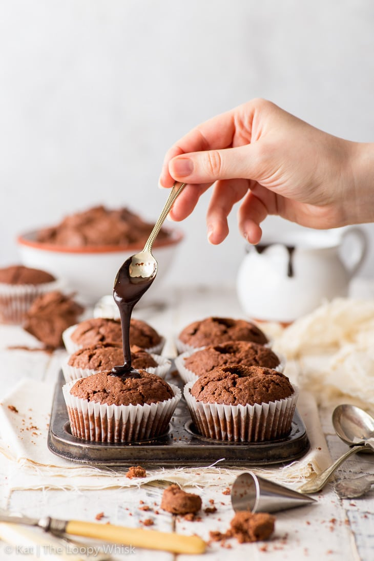 Filling the holes in the cupcakes with chocolate fudge sauce.